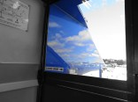 A mirror of the surrounding area where a city cat is sailing along the Brisbane River...off the bulkhead of the vessel.